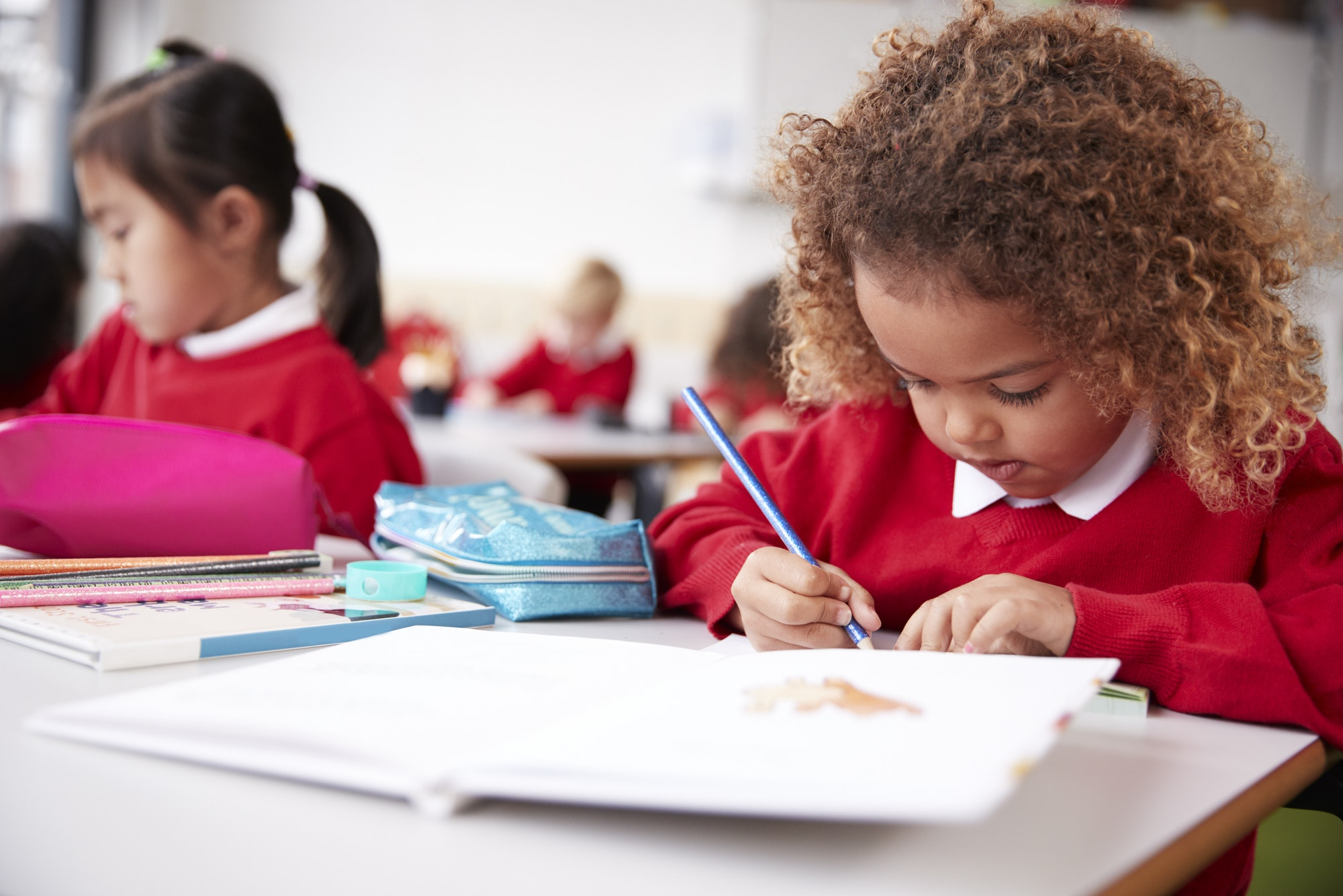 Mixed race schoolgirl sitting at a desk in an infant school classroom drawing, close up