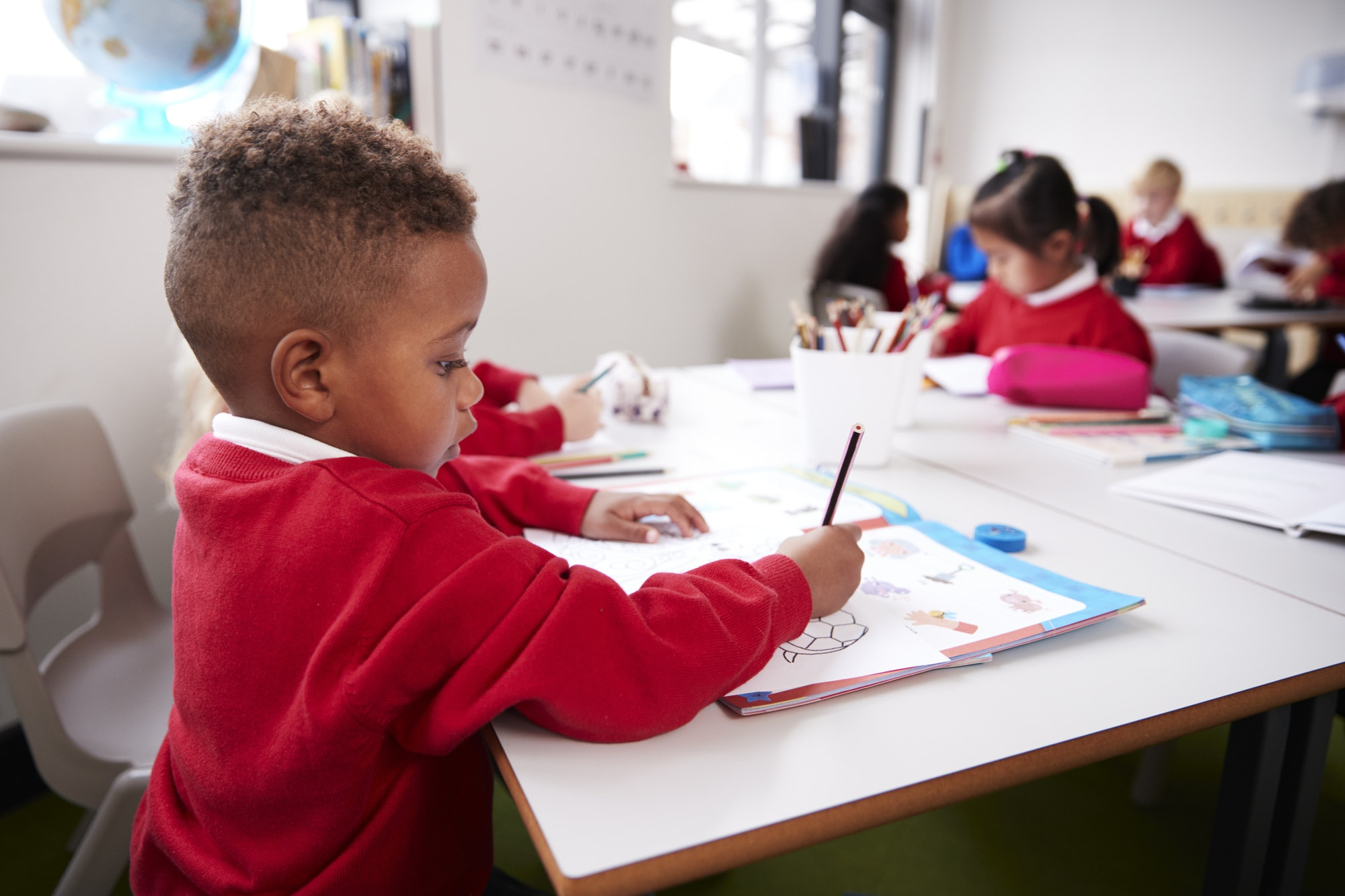 Young black schoolboy wearing school uniform sitting at a desk in an infant school classroom drawing