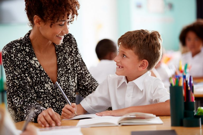 Woman Elementary School Teacher Giving Male Pupil Wearing Uniform One To One Support In Classroom